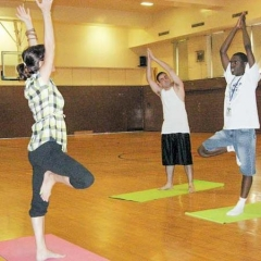 Instructor and students reach to the sky, balancing on one leg