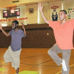 Two students show great balance, hands up and poised on one leg.