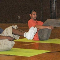 Two students perform a floor pose, practicing both balance and strength.