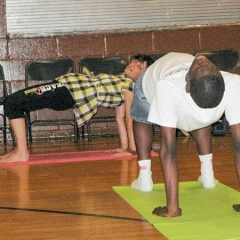 Instructor and student stretch upward from their mats to practice a table pose.