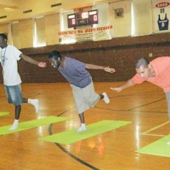 Four students practice balance, leaning forward on one leg, arms out.