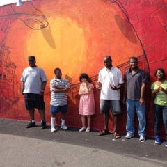 Participants stand in front of an orange graffiti style painted wall.