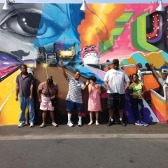 Participants wave in front of Coney Island Art Walls