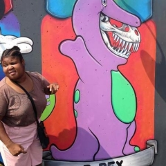A participant takes a picture in front of a graffiti of Barney.