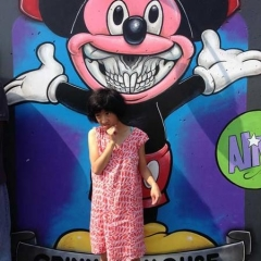 A participant stands in front of a graffiti of Mickey Mouse.