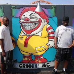 Two participants stand around a graffiti of Roland McDonald.