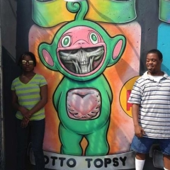 Participants pose around a graffiti of a Telly Tubby.