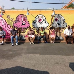 Participants sit in front of a graffiti wall.