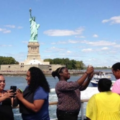 Participants taking selfie photos in front of Statue of Liberty.