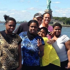Participants pose for a group shot as the boat passes Statue of Liberty.