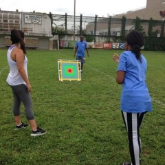 A participant throwing a ball at a bullseye.