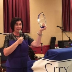 Sophia Rossovsky, City Access New York Executive Director, is holding up the crystal award.