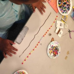 A participant in the middle of making a necklace.