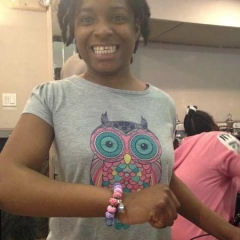 A smiling participant showcasing a bracelet she just made in the art class.