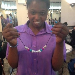 A participant holding up a necklace.