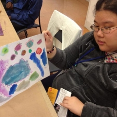 A participant showing her painting for the camera.