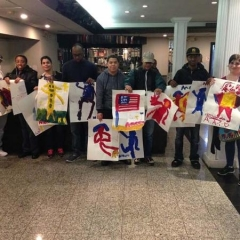 Participants pose with art work they created during an art session.