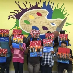 Participants holding up their completed paintings of the New York skyline.