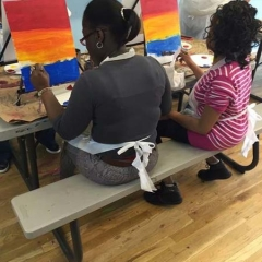 Two participants learning painting techniques.