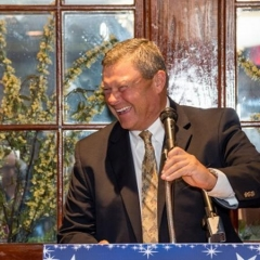 Bob Bentson, gala honoree, accepts an award.  ID: Bob smiles at the podium.