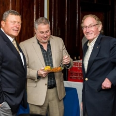 Bob Bentson and friends.  ID: The men stand sampling hors d'oeuvres.