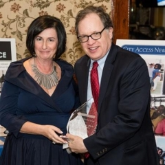 Sophia Rossovsky hands an award to Andy Fisher, Director of Lavelle Fund for the Blind.  ID: Sophia and Andy are holding a crystal award.