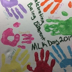 Art painting with different color hand prints to symbolize our differences.