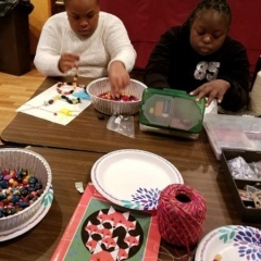 Two participants at an art class.  ID: A participant on the left is working on a necklace while the other one is looking inside a box with art supplies.