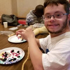 DayHab participant smiles for the camera.  ID: The participant is sitting at a table and is adding beads to a necklace that he is making.
