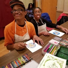 Two participants at an art class.  ID: A participant smiles while displaying his artwork.