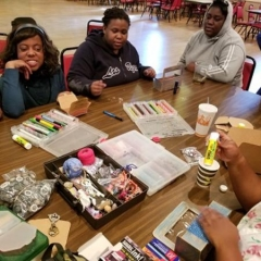 Group of participants at an art class. ID: Participants sit around a table full of various art supplies.