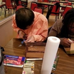 Participant in an art class.  ID: A participant leans over a table as he is working on his art project.