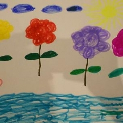 A drawing made for the art contest.  ID: A picture of flowers, clouds, and an ocean in the front.