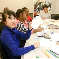 Participants making art pieces for the art contest submission.  ID: A participant wearing dark blue is at the front.