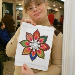 A participant holding up her artwork.  ID: An intricate drawing of a flower.