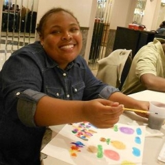 A participant working on her art project.  ID: A smiling participant holds a pencil over a drawing.