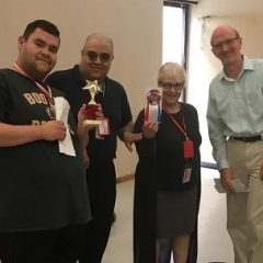 A participant posing with Brooklyn DDC representatives.  ID: A participant holding up a star shaped award.