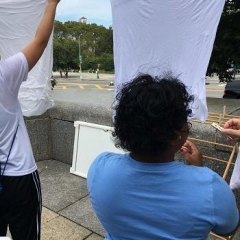Participants hanging linens to dry.  ID: A participant is using clothes pins.