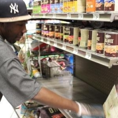 A participant is cleaning Petco product shelves.  ID: A participant is wearing a gray shirt, a black baseball cap, and rubber gloves.