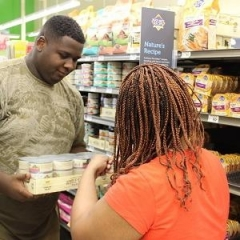 Two participants are working together to stack shelves at Petco.  ID: The participants are holding a case of canned goods.