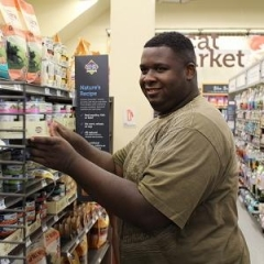 A participant smiles as he is stacking shelves at Petco.  ID: A man stands in an isle of Petco.