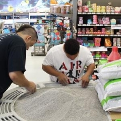Two participants are working on a kitty litter display.  ID: One participant is wearing a black t-shirt and another one a white one.