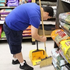 A participant is sweeping a floor at Petco.  ID: A participant wearing a blue shirt is bending down to sweep up the floor.