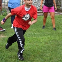 A participant is running through a ballpark.  ID: A participant is wearing a red shirt with a picture of a soccer ball on it.