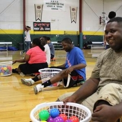 Participants with baskets full of colorful balls.  ID: Participants sitting on a floor of a basketball court.