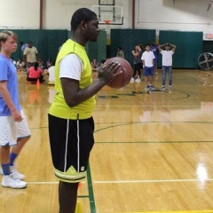 Participant preparing for a freethrow.  ID: A participant wearing a bright yellow jersey is getting ready to make a shot.