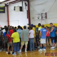 A group of participants are looking up at a score board.  ID: Participants assembled on a basketball court.