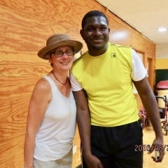 A participant and a board member pose for a picture.  ID: The board member is wearing a white shirt and a hat.  The participant is wearing a bright yellow shirt.
