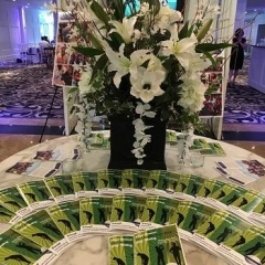 Golf outing brochures lined up in front of a bouquet of flowers.