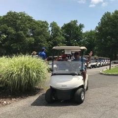 Event participants riding in a golf cart.